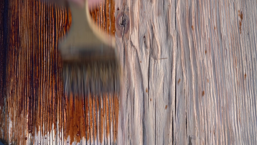 Stain wood. Brush stain process. Close-up Wood painting wa bith rush with the brown color. Royalty-Free Stock Footage #1061691436