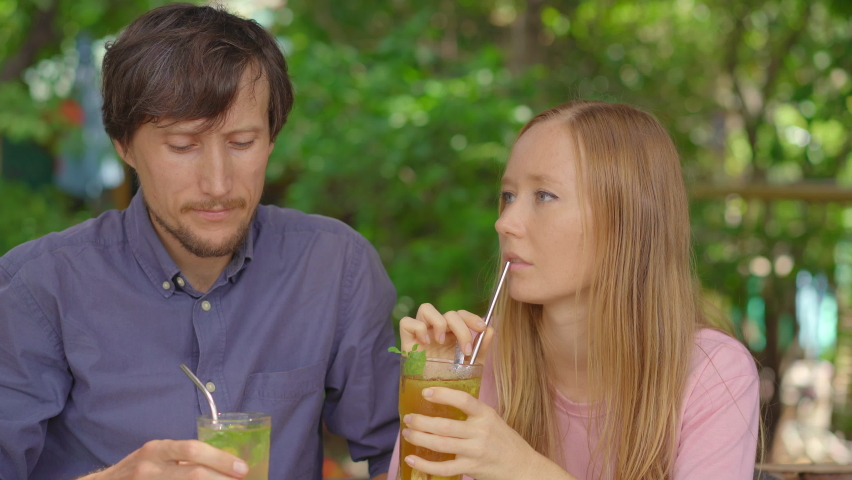 In a cafe young couple have a chat. They drink their drinks using reusabla steel straws. Concept of reducing the use single plastic Royalty-Free Stock Footage #1061695168