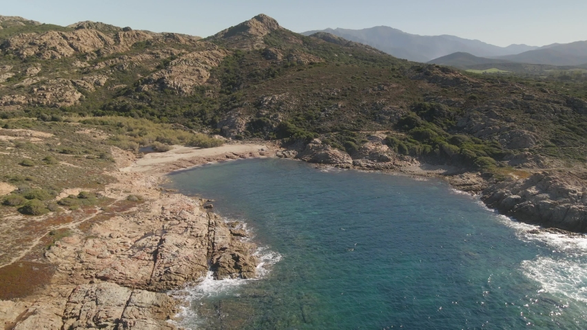 Aerial view of the translucent turquoise Mediterranean sea washing onto rocky outcrops and small sandy beach in a cove on the Agriates coast near Ostriconi in the Balagne region of Corsica