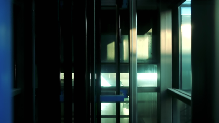 Modern glass elevator descending to the ground floor. Elevator going down. Royalty-Free Stock Footage #1061700178