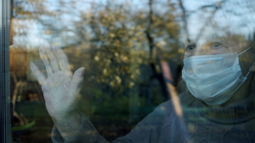 Portrait in the window of an elderly woman in a medical protective mask who put her hand on the glass and waiting for medics or relatives to help her   Shutterstock HD Video #1061700256