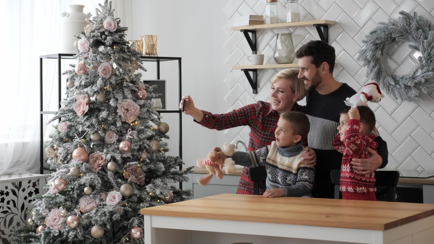 Beautiful married couple with children using smart phone talking to friends congratulates Merry Christmas by video call conference app. Modern technology New Year 2021 congrats. | Shutterstock HD Video #1061700421