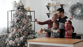 Beautiful married couple with children using smart phone talking to friends congratulates Merry Christmas by video call conference app. Modern technology New Year 2021 congrats.