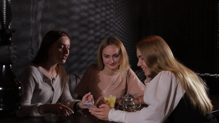 Three girlfriends drink tea and talk over dinner. Cheerful young students chatting and having fun sitting in a cozy cafe.