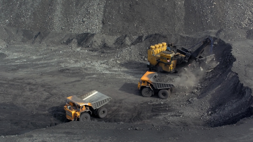 A large bucket excavator loads coal into a large dump truck 3