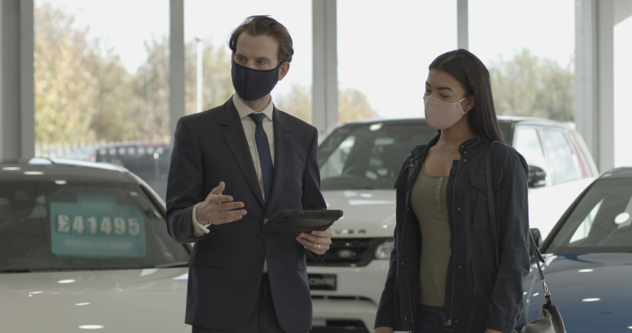 Car sales person talking to customer wearing protective face mask in car dealership showroom and looking at digital tablet