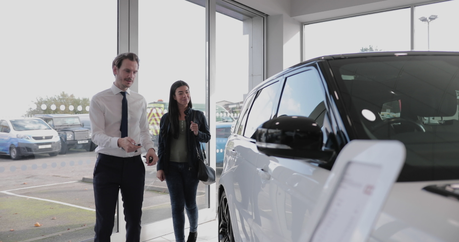 Car salesman showing customer car in automotive dealership showroom Royalty-Free Stock Footage #1061710210
