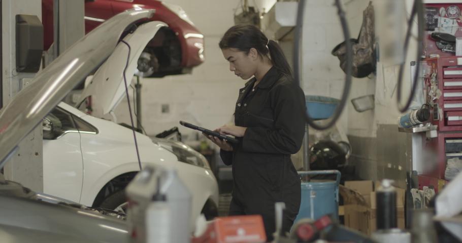 Female car mechanic looking under vehicle using digital tablet in automotive workshop