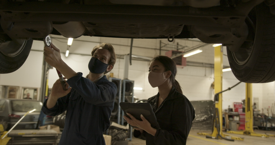 Car mechanic and trainee with protective face mask looking at car in auto repair workshop using digital tablet