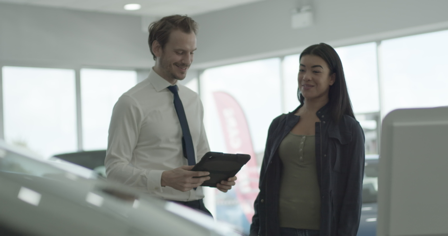 Car sales person talking to customer in car dealership showroom, looking at digital tablet and vehicle
