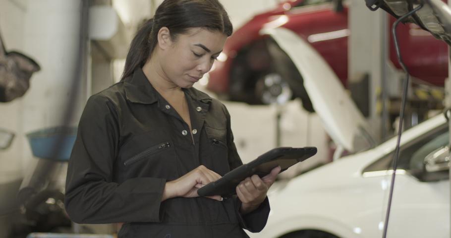 Female car mechanic looking under vehicle bonnet using digital tablet in automotive repair workshop