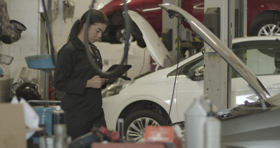 Female car mechanic looking under vehicle bonnet using digital tablet in workshop