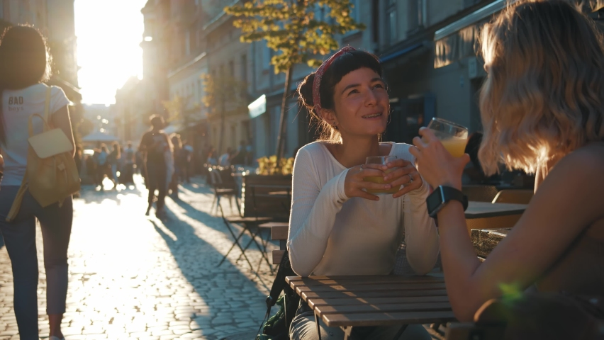 Two attractive caucasian girls sitting at the street cafe at pleasant sunset drinking juice or coffee, communicate and sharing stories while drinking orange juice, spending relax outdoor evening.