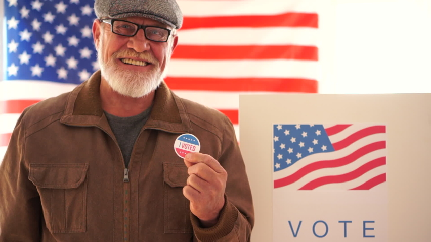 American retired masked to vote in 2020 US elections in the voting booth. An elderly man with glasses and a gray beard votes at a polling station holds a sticker in his hand and smiles proudly
