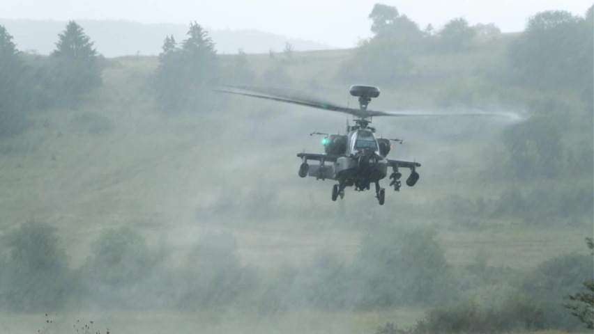 CIRCA 2020 - U.S. Army AH-64 Apache Attack helicopter lands in downpour NATO Combined Resolve exercise in Germany.
