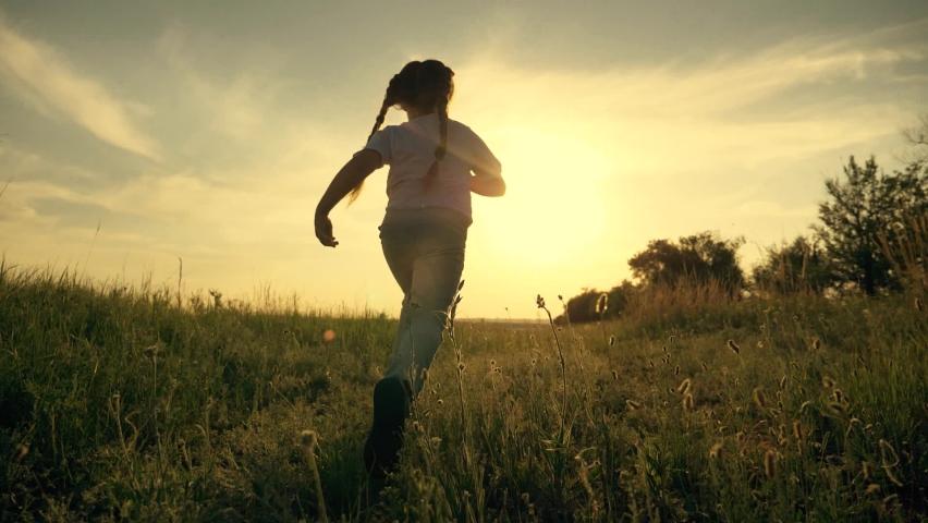 Girl is run along road. Childdream concept. Happy little girl at sunset. Kid run across field. Happy kid in field at sunset. Girl run along road at sunset. Happy family concept. Dream of child. Royalty-Free Stock Footage #1061732350