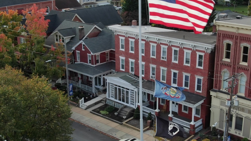 Manheim , PA / United States - 10 18 2020: Aerial reveal shot of American flag, Pennsylvania state, POW, MIA flags in Small Town America, USA. Honor veterans and military service.