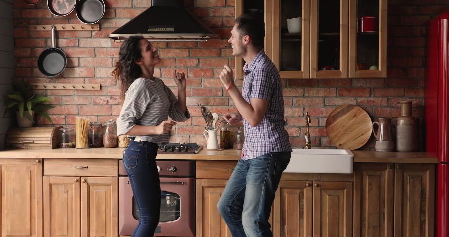 Couple dancing in cozy kitchen holding hands enjoy hobby and funny active weekend together, husband lifted wife in arms and circles spinning her in dance. Family celebrate move day to new home concept Royalty-Free Stock Footage #1061743366