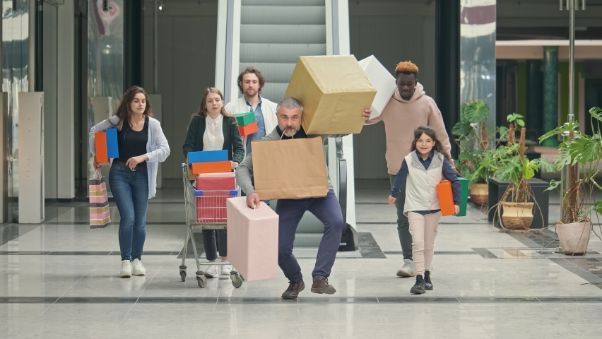 A Group of Contented Shopaholics with Shopping Bags and a Trolley Running Through the Mall, Rushing to Shop on Black Friday. Crazy Shopping at Big Sales. Christmas time. Funny concept. Royalty-Free Stock Footage #1061745919