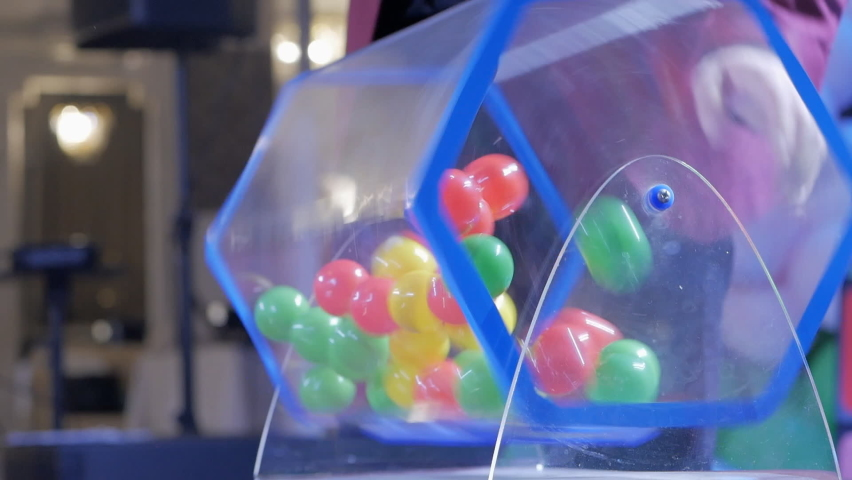 Plastic balls are mixed in a bingo drum. the drawing of prizes using a Lotto.