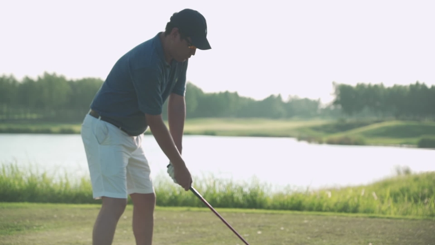 Young Asian adult male player driving golf on green grass professional golf course. Golfer with golf club, golfer swinging and hitting golf ball on beautiful course at sunset by the lake, sunset pond