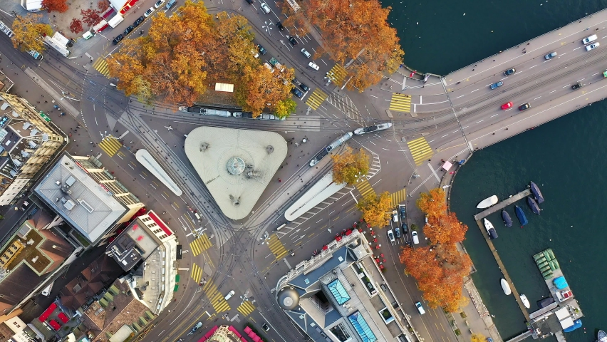 Top down view of a major intersection with tramway and cars where the Limmat river meet the lake in Zurich downtown, Switzerland largest city. Shot with a downward and rotation motion Royalty-Free Stock Footage #1061764855