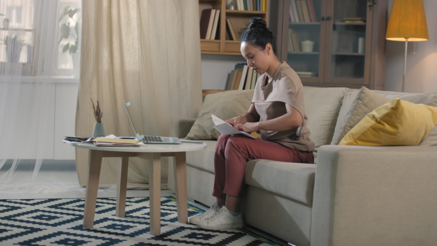 Happy young mixed race woman sealing last envelope after doing financial paperwork reclining on sofa chilling Royalty-Free Stock Footage #1061767684