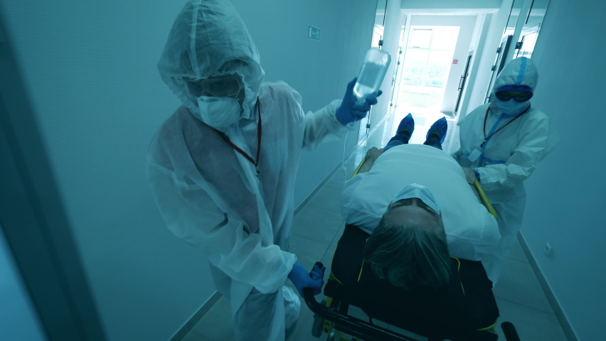 COVID-19 patient in coronavirus hospital. Doctors are transporting a patient on a medical trolley Royalty-Free Stock Footage #1061770555