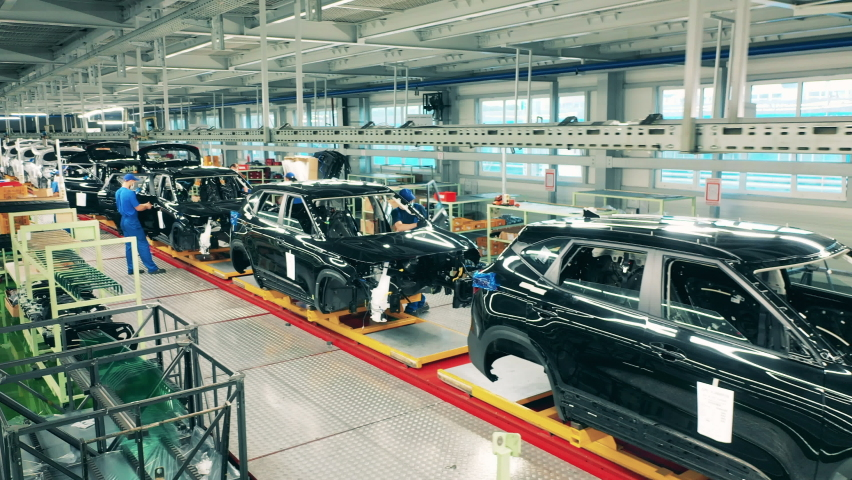 People working at a conveyor at car factory. Automotive industry, automobile production line.