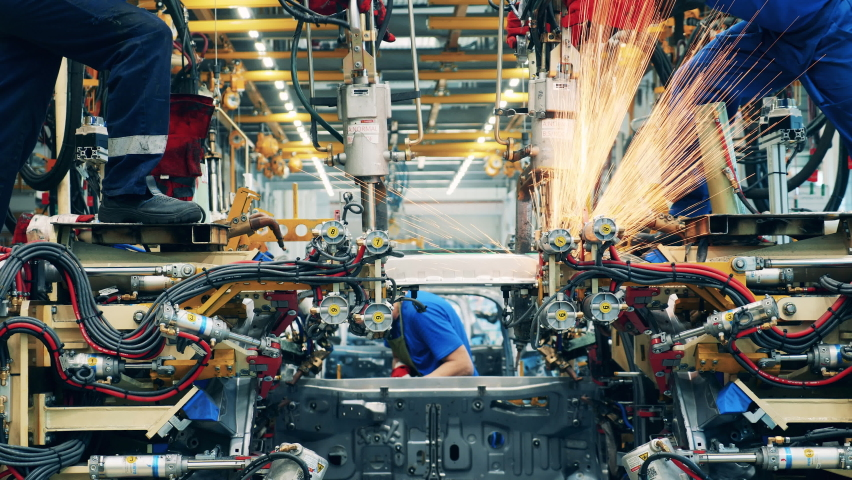 Several factory workers welding a car body at a car factory Royalty-Free Stock Footage #1061770891