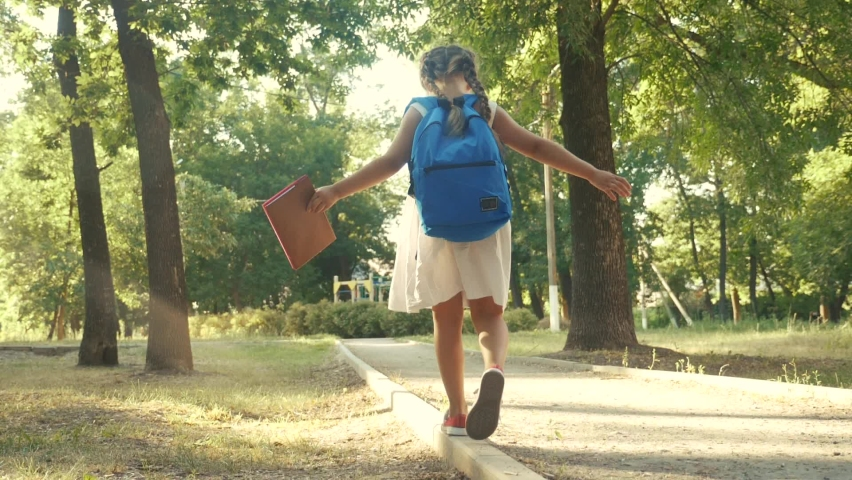 Schoolgirl goes to school through the park along the path. kid dream concept. people in the park. schoolgirl goes school in the park education. schoolgirl walk after class with a backpack and book