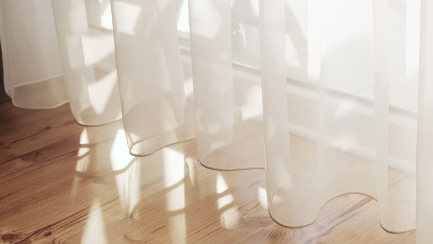 Transparent white curtain tulle moves from the wind from an open window. Sunny day, the sun's rays sunlight penetrate the room. Royalty-Free Stock Footage #1061778502