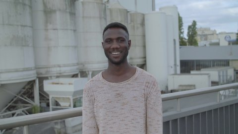 Handsome African Man Posing for Camera on Industrial Background