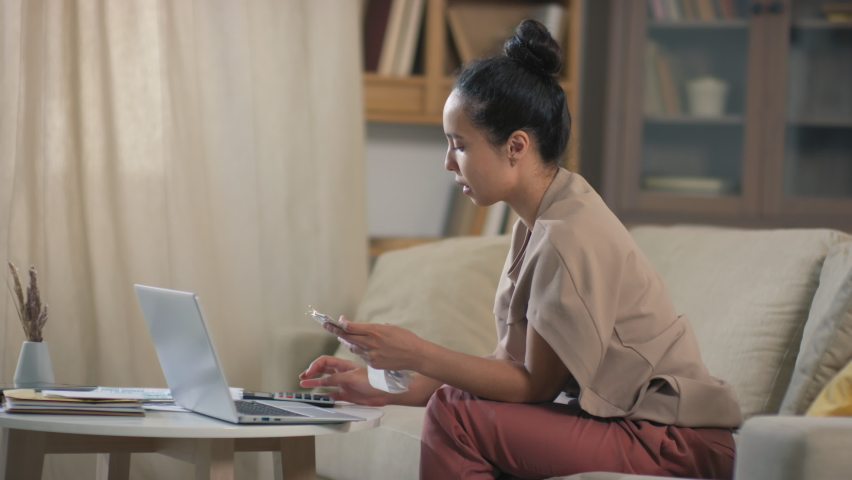 Mixed race woman finished financial analysis of budget and counting payments on calculator finally reclining on sofa smiling Royalty-Free Stock Footage #1061783122