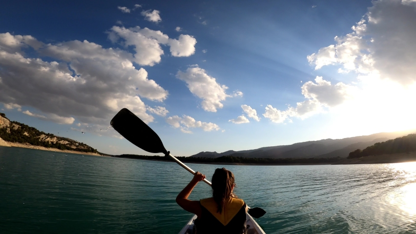 Woman kayak rowing. Kayaker woman and man kayaking in beautiful landscape at Embalse de la Bolera, Spain. Kayakers practice sports in a kayak at the lake. Aquatic sports during summer