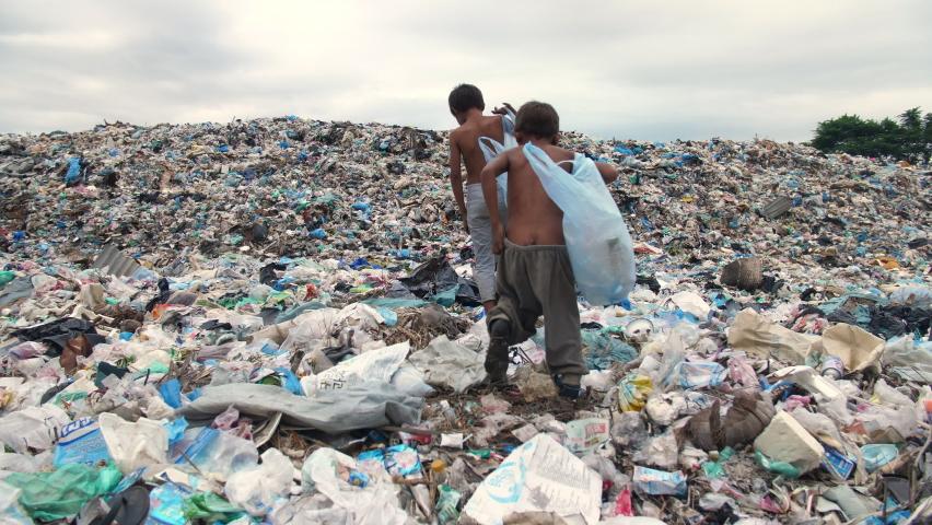 Poor Children Walking On Garbage Dump