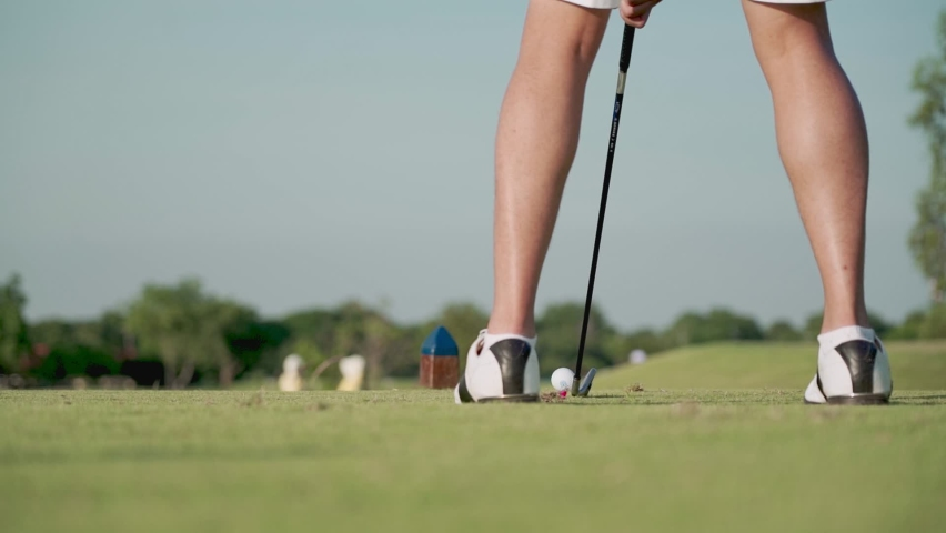 low angle shot lower body of Young adult male golfer driving tee off golf on green grass professional golf course. rear view golfer swinging and hitting golf ball on beautiful grass, slow motion Royalty-Free Stock Footage #1061786257