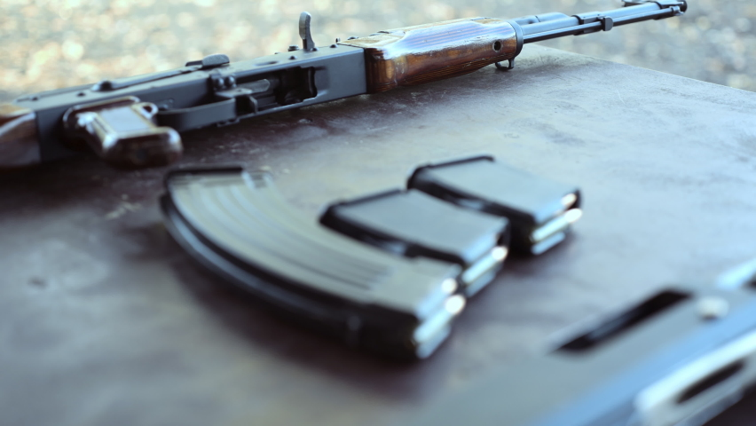 AK 47 assault rifle and a magazine with bullets. A man takes a  assault rifle from the table. Close-up.