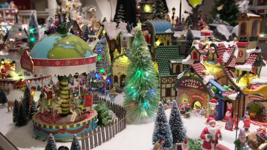 Christmas decor in  store window. Winter village in miniature. Christmas decor in store window. dynamic toy winter town, carousel, residents, snow, Santa Claus and trees. festive atmosphere Royalty-Free Stock Footage #1061795464