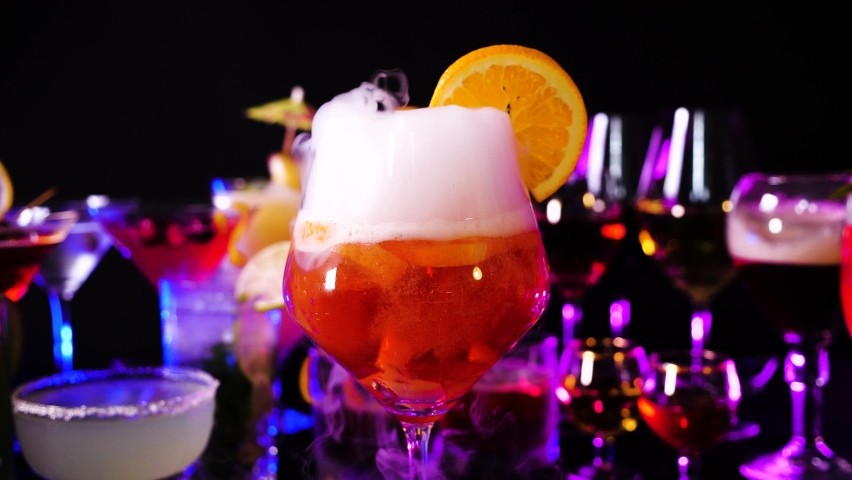 Aperol spritz drink with dry ice at bar counter close up. Bartender show and prepared cocktail with dry ice on a cocktail bar background. Colorful various drinks in a bar with dry ice smoke effect. | Shutterstock HD Video #1061796862