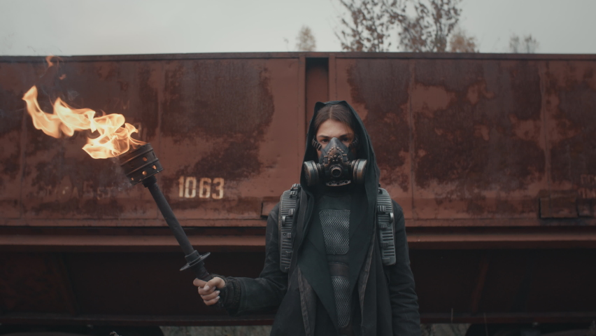 Woman in cyberpunk suit and gas mask standing by rusty train carriage hold burning torch in hand and looking into camera. Dystopian warrior concept, female survivor in abandoned city. Post apocalypse Royalty-Free Stock Footage #1061799514