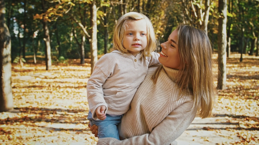Young mom in casual clothes is smiling, holding little daughter in arms and tickling her during their walk in autumn park. Sunny day, yellow foliage. Happy family time. Close up, slow motion