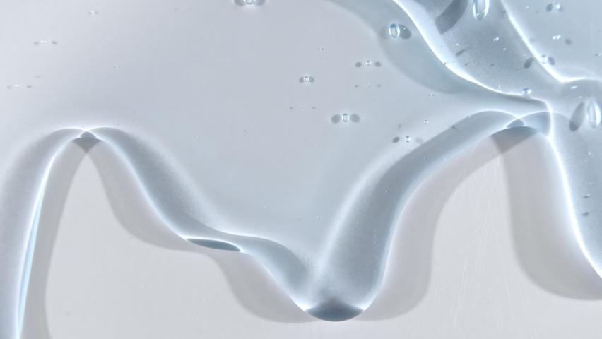 Transparent liquid gel cream with micro Bubbles as it slowly slides down. Macro Shot