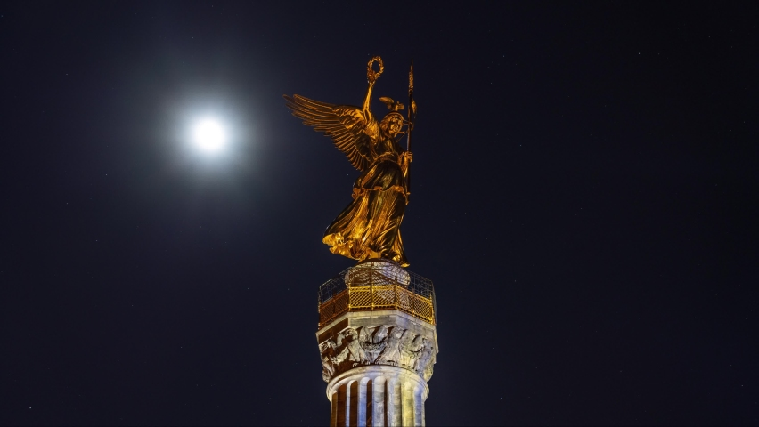 Time lapse of the golden angel of the Siegessaeule (Victory Column) with full moon in Berlin, Germany
