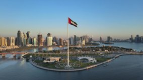 Aerial view of the Flag of the United Arab Emirates waving in the air, the Blue sky in Background, The national symbol of UAE over Sharjah's Flag Island, United Arab Emirates, 4K Video