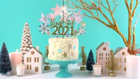 Happy New Year's Eve celebration cake on cake stand in blue white and gold theme decorated with stars and humorous, Thank God It's 2021, cake topper. Full party table setting with burning sparkler.