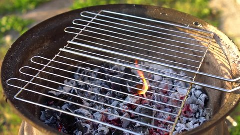 The cook puts the fish on the barbecue net and it slips off. The chef puts the crucian carp on the grill. Fish is fried on the charcoal grill. Grilled dishes.