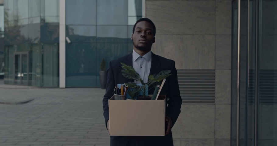 Depressed african american male office worker leaving business center building with box of personal stuff. Businessman lost job. Fired man walking outdoor. Depressed jobless person. Unemployment.