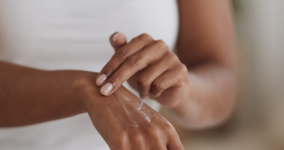 Female hands care. Close up shot of african american lady applying cream on hand skin, slow motion
