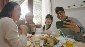 Candid of happy asian family having fun on dining table at home holding mobile video call online and selfie or take photo shoot group with smile and laugh together.